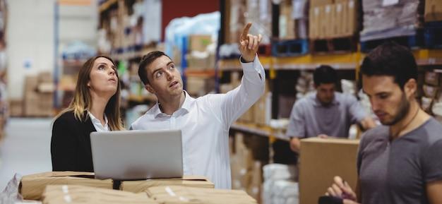 Retrato de gerentes de almacén sonrientes usando laptop