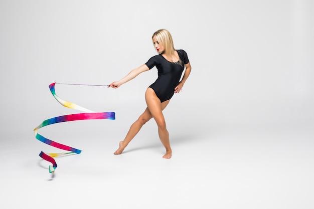 El retrato de gimnasta joven hermosa entrenamiento calilisthenics ejercicio con cinta. concepto de gimnasia de arte.