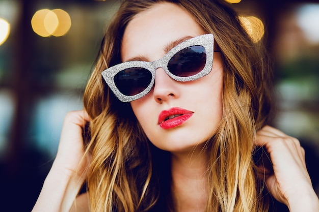 Retrato de glamour elegante dama rubia con gafas de sol retro cool