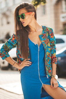 Retrato de glamour hermosa morena moderna modelo adolescente en verano hipster azul vestido y chaqueta. chica posando en la calle. mujer en gafas de sol