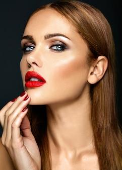 Retrato de glamour sensual de mujer hermosa dama modelo con labios rojos de color y cara de piel limpia y saludable