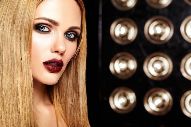 Retrato de glamour sensual de mujer hermosa modelo con maquillaje diario fresco con color de labios rosados y piel limpia y sana sobre fondo de luces de estudio