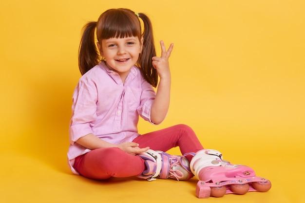 Retrato de gracioso niño pequeño haciendo gestos, levantando dos dedos, sonriendo sinceramente, descansando, sentado en el piso, usando patines, con dos coletas, estando solo. concepto de juegos