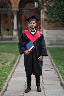 Retrato de graduado indio en toga de graduación en campus universitario.