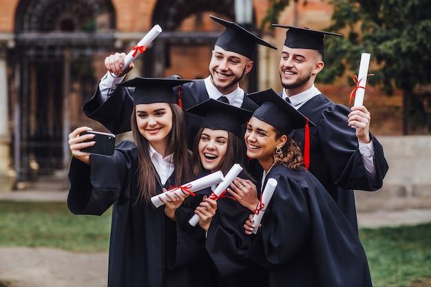 Retrato de graduados multirraciales con diploma y haciendo selfie en teléfono lifestule