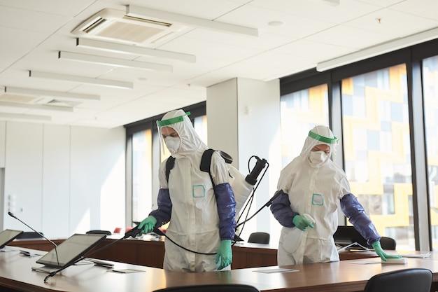 Retrato de gran angular de dos trabajadores de saneamiento vistiendo trajes de materiales peligrosos, limpieza y desinfección de la sala de conferencias en la oficina,