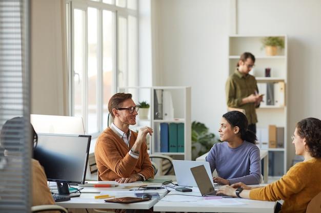 Retrato de gran angular del equipo de jóvenes empresarios discutiendo el proyecto de inicio mientras trabajaba en el escritorio en el interior de la oficina blanca, espacio de copia