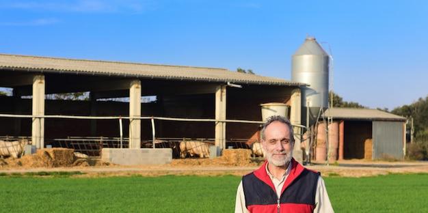 Retrato de un granjero en el campo con una granja al atardecer