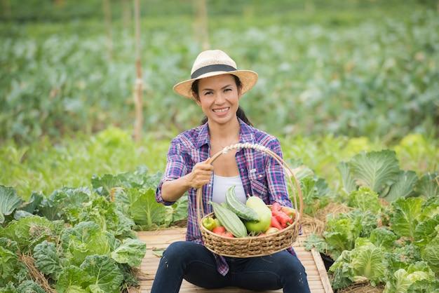 Retrato del granjero de sexo femenino feliz que sostiene una cesta de verduras en la granja