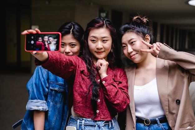 Retrato de un grupo de amigas asiáticas tomando un selfie