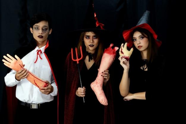 Retrato de grupo de amigos adultos jóvenes asiáticos usan disfraz de halloween para ser brujas y personaje de drácula. celebración de halloween y concepto de vacaciones internacionales.