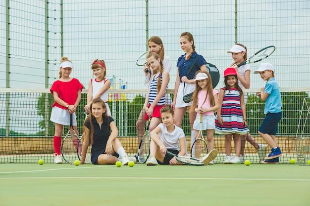 Retrato de un grupo de chicas como tenistas sosteniendo la raqueta de tenis contra la hierba verde de la cancha al aire libre