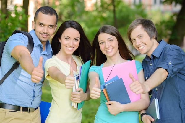 Retrato de grupo de cuatro estudiantes alegres sonrientes.