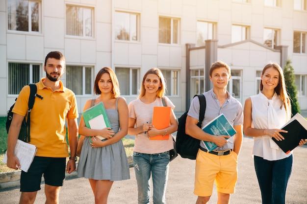 Retrato de grupo de estudiantes felices en traje casual con libros mientras está de pie