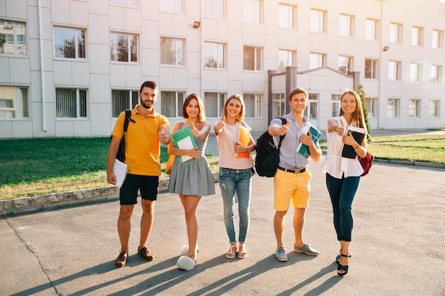 Retrato de un grupo de estudiantes felices en traje casual con libros mostrando los pulgares para arriba