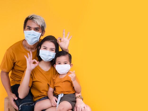 Retrato del grupo familiar que muestra un signo aceptable y usa una máscara protectora tratando de protegerse del virus
