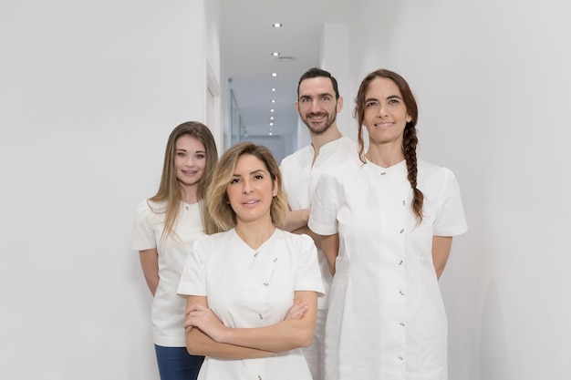 Retrato del grupo feliz confiado de doctores que se colocan en la oficina médica