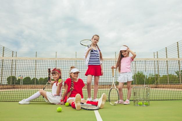 Retrato del grupo de muchachas como jugadores de tenis que sostienen las raquetas de tenis contra la hierba verde de la corte al aire libre.