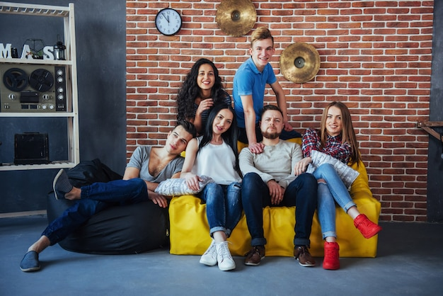Retrato de grupo de niños y niñas multiétnicos con ropa colorida de moda con un amigo posando en una pared de ladrillo, gente de estilo urbano divirtiéndose, s sobre el estilo de vida de la juventud