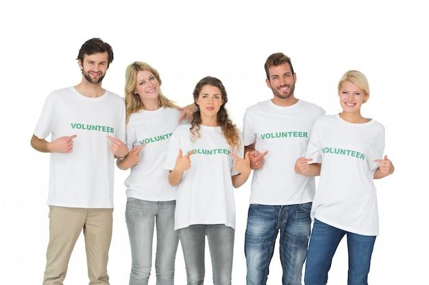 Retrato de grupo de voluntarios felices apuntando a sí mismos sobre fondo blanco
