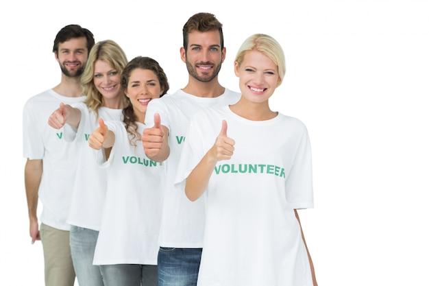 Retrato de grupo de voluntarios felices gesticulando pulgares arriba