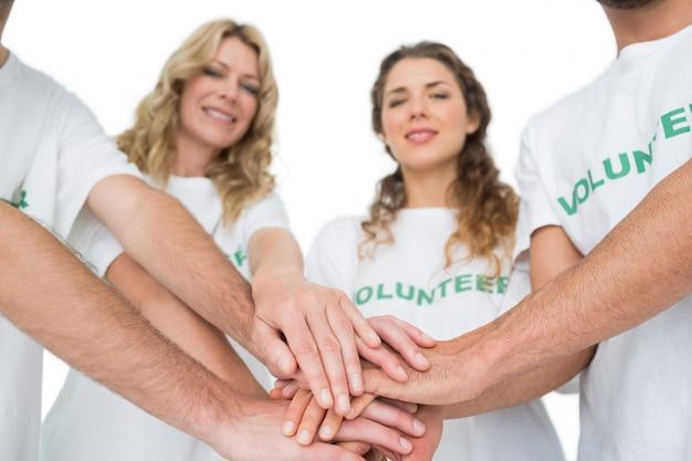 Retrato de grupo de voluntarios felices con las manos juntas