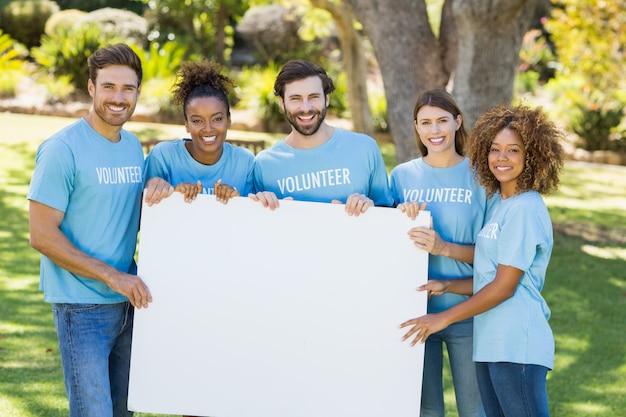 Retrato de grupo de voluntarios con hoja en blanco