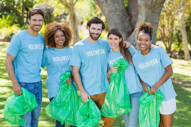 Retrato de grupo de voluntarios posando mientras recoge basura