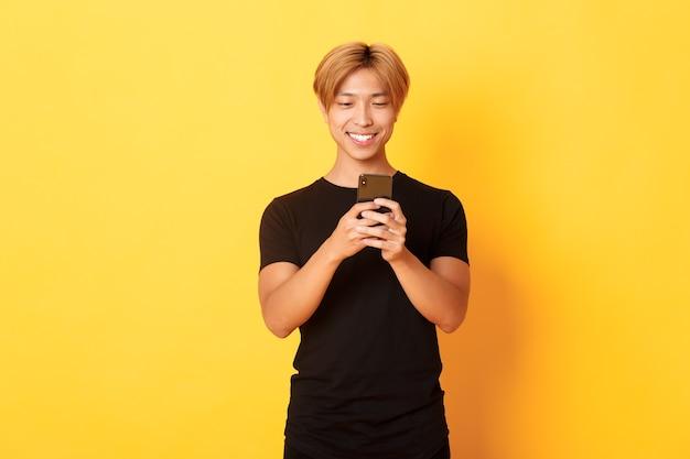 Retrato de guapo asiático elegante con cabello rubio, usando teléfono móvil y sonriente, pared amarilla
