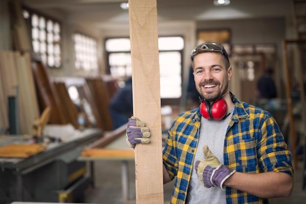 Retrato de guapo carpintero sonriente con material de madera en el taller sosteniendo thumbs up