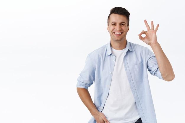 Retrato de un guapo chico de familia satisfecho con camisa sobre camiseta, muestra una confirmación aceptable o un gesto de seguridad, sonriendo complacido, recomienda un producto de buena calidad, da permiso, garantiza la calidad