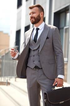 Retrato de guapo empresario caucásico con bolsa en reunión de negocios