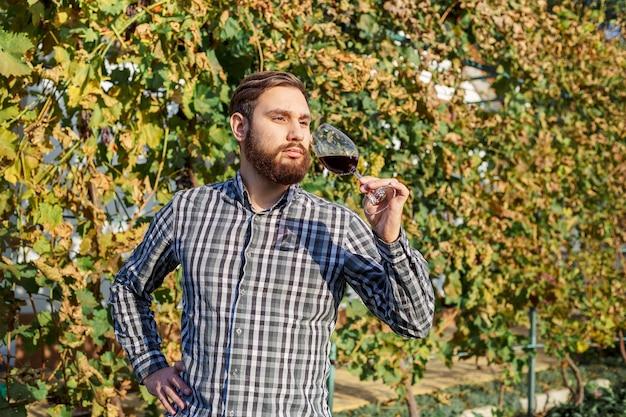 Retrato de guapo enólogo sosteniendo en su mano una copa de vino tinto y probándolo, comprobando la calidad del vino mientras está de pie en los viñedos