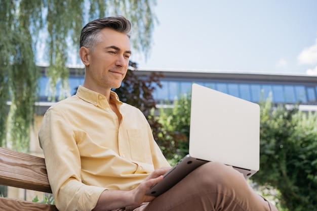 Retrato de guapo escritor de mediana edad con portátil, trabajando al aire libre