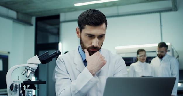 Retrato del guapo hombre caucásico científico haciendo una investigación en la computadora portátil y análisis mientras mira en el microscopio en el laboratorio.