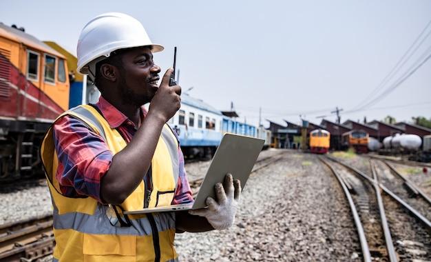 Retrato de guapo ingeniero africano-americano con walkie talkie para el control del trabajo con un portátil delante del garaje del tren