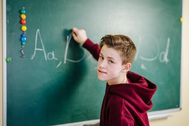 Retrato de guapo joven estudiante masculino escribiendo en la pizarra