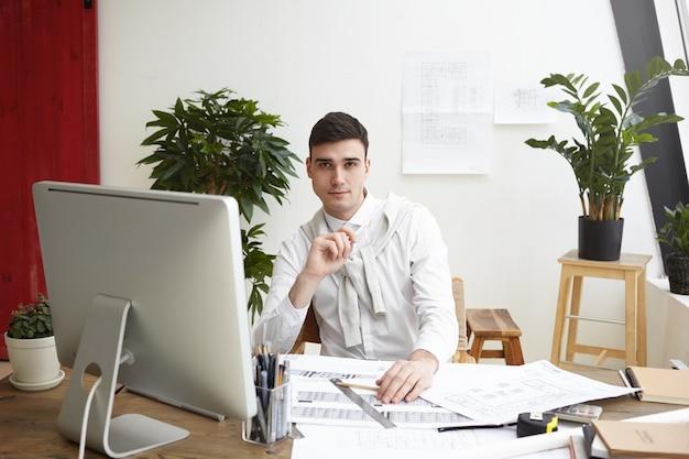 Retrato de guapo joven ingeniero confiado haciendo dibujos de proyecto de vivienda residencial o edificio comercial, sentado en su escritorio con planos, herramientas informáticas y de ingeniería