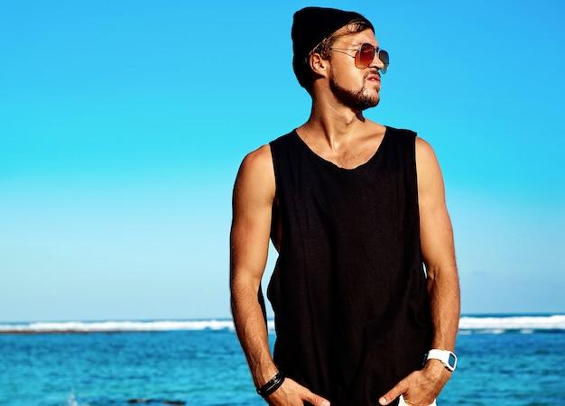 Retrato de guapo modelo de hombre de moda tomando el sol con ropa casual en camiseta negra y gafas de sol posando