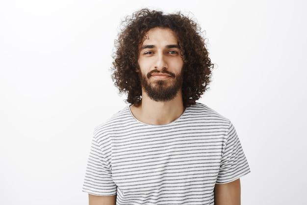 Retrato de guapo novio creativo seguro con cabello oscuro y rizado, de pie con una leve sonrisa y expresión segura de sí mismo