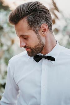 Retrato de guapo novio en su boda en la playa
