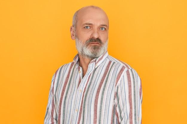 Retrato de guapo pensionista masculino europeo con cabeza calva y espesa barba gris mirando a cámara con expresión facial sospechosa dudosa, sin confiar en usted. reacciones y emociones humanas