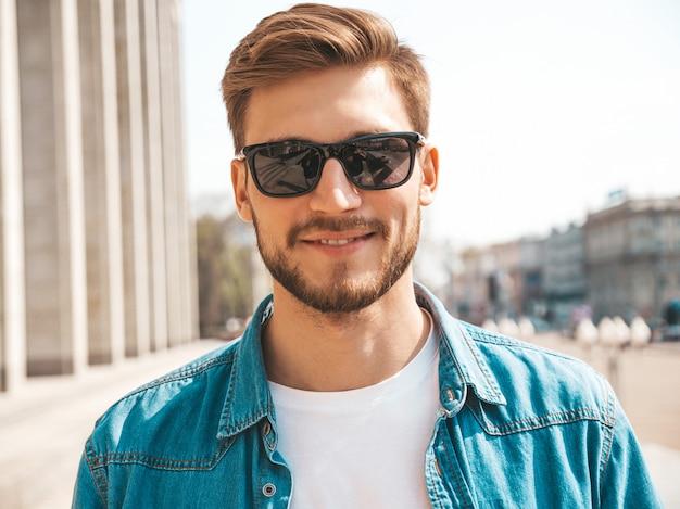 Retrato de guapo sonriente elegante hipster lumbersexual empresario modelo. hombre vestido con ropa de chaqueta de jeans.