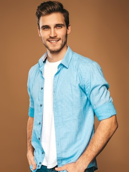 Retrato de guapo sonriente elegante joven modelo vestido con camisa azul ropa. hombre de moda posando
