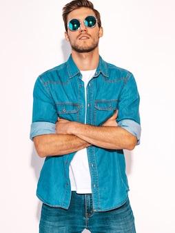 Retrato de guapo sonriente elegante joven modelo vestido con ropa de jeans y gafas de sol. hombre de moda