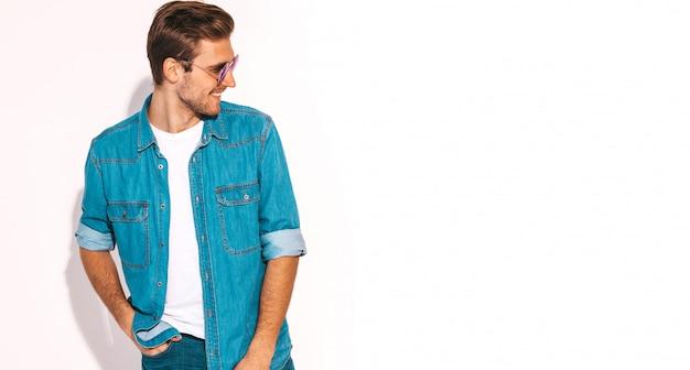 Retrato de guapo sonriente elegante joven modelo vestido con ropa de jeans. hombre de moda con gafas de sol.