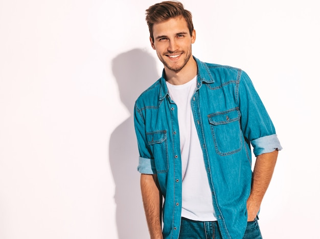 Retrato de guapo sonriente elegante joven modelo vestido con ropa de jeans. hombre de moda