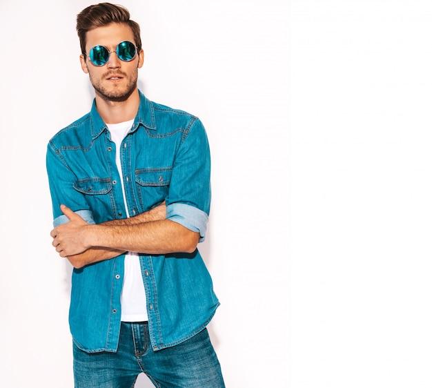 Retrato de guapo sonriente elegante joven modelo vistiendo ropa de jeans y gafas de sol. hombre de moda. brazos cruzados
