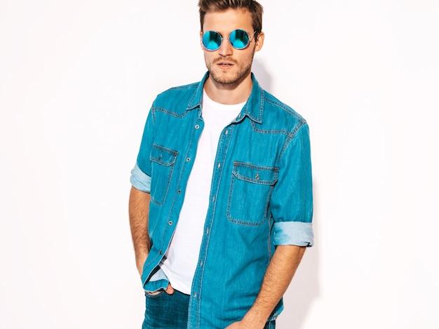 Retrato de guapo sonriente elegante joven modelo vistiendo ropa de jeans y gafas de sol. hombre de moda