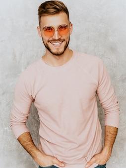 Retrato de guapo sonriente joven modelo vistiendo ropa casual verano rosa. hombre elegante moda posando en gafas de sol redondas